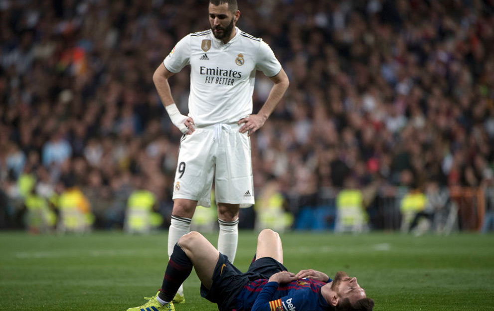 Barcelona's Argentinian forward Lionel Messi lies on the field beside Real Madrid's French forward Karim Benzema (TOP) during the Spanish league football match between Real Madrid CF and FC Barcelona at the Santiago Bernabeu stadium in Madrid on March 2, 2019. (Photo by CURTO DE LA TORRE / AFP) (Photo credit should read CURTO DE LA TORRE/AFP via Getty Images)